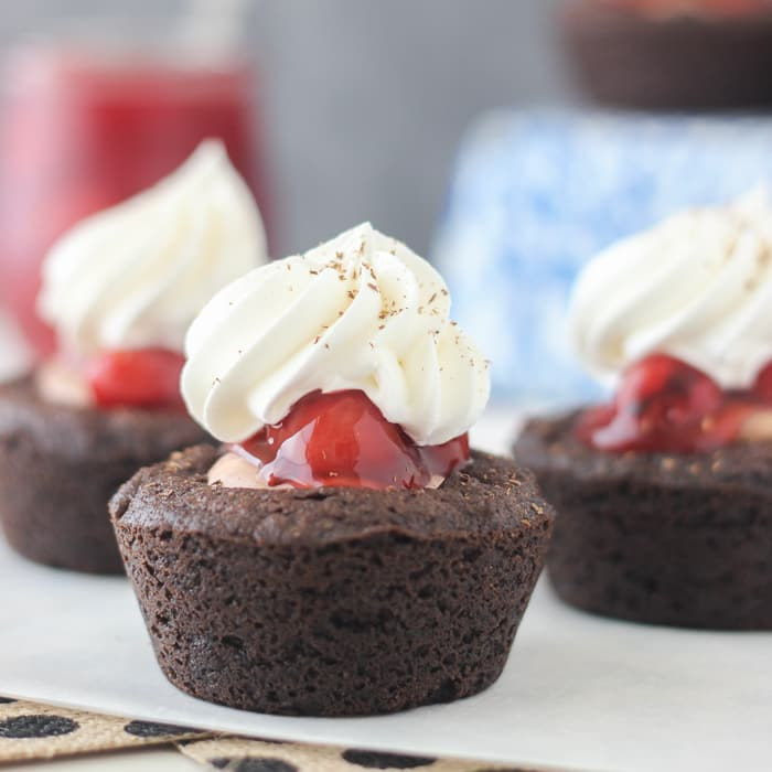 These Black Forest Cookie Cups are a soft baked chocolate cookie filled with chocolate mousse and cherry pie filling. All topped with fresh whipped cream and chocolate shavings.