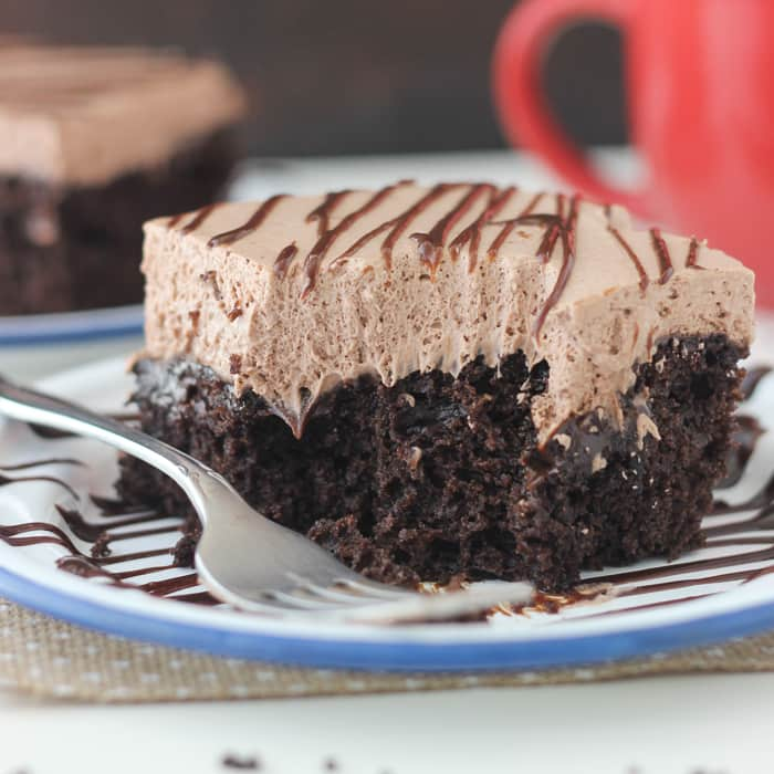 Hot Chocolate Poke Cake: Rich chocolate cake made with hot chocolate, soaked in hot fudge and topped with hot chocolate whipped cream.