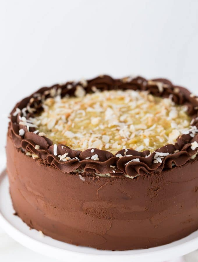 This German Chocolate Cake is four layers of moist chocolate cake soaked in rum syrup and filled with sweet coconut custard filling and wrapped beautifully in a chocolate ganache frosting.