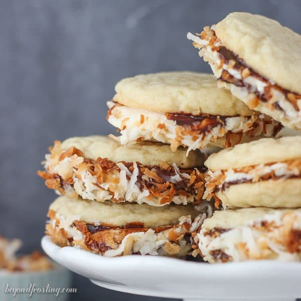 Dig into these Samoa Cookie Sandwiches. All you favorite parts of a Samoa cookie come to life. Soft, buttery sugar cookies with layers of hot fudge, caramel cream cheese and toasted coconut.