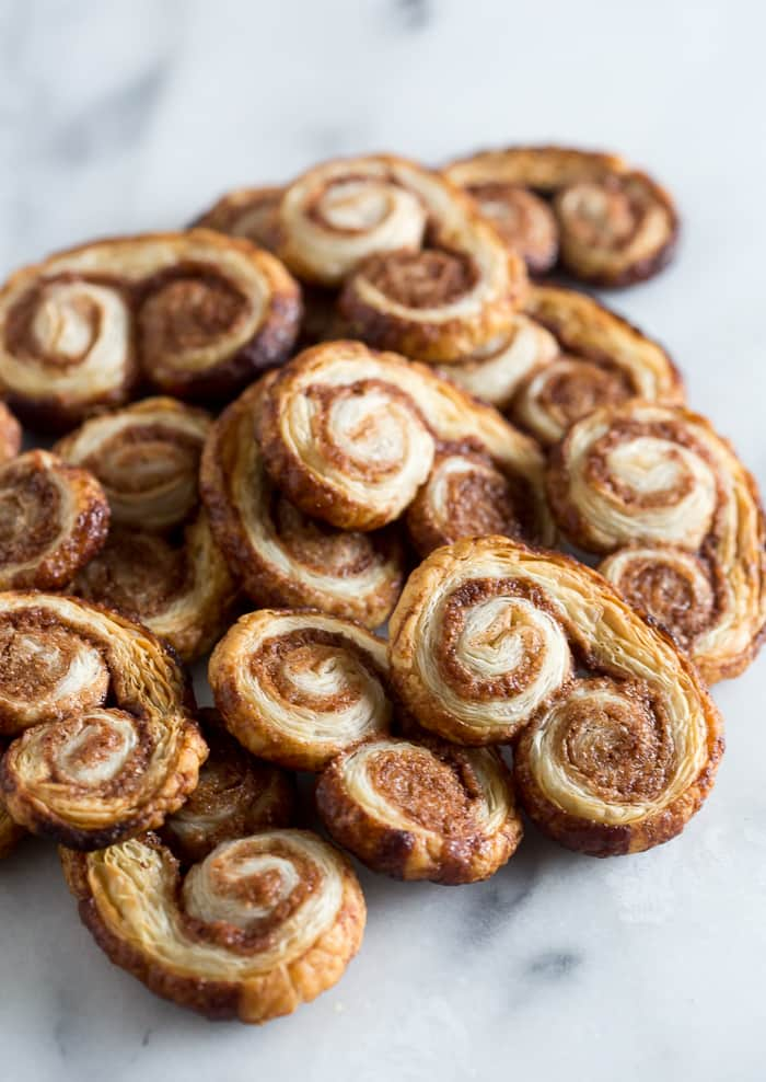 These cinnamon sugar palmiers are ready in under 20 minutes and are sure to please everyone. Perfectly sweet, crunchy and made with store bought puff pastry. You'll love these cookies!