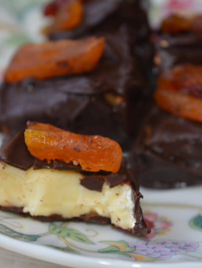 A chocolate covered slice of brie with dried fruit on top. there are several on a plate.
