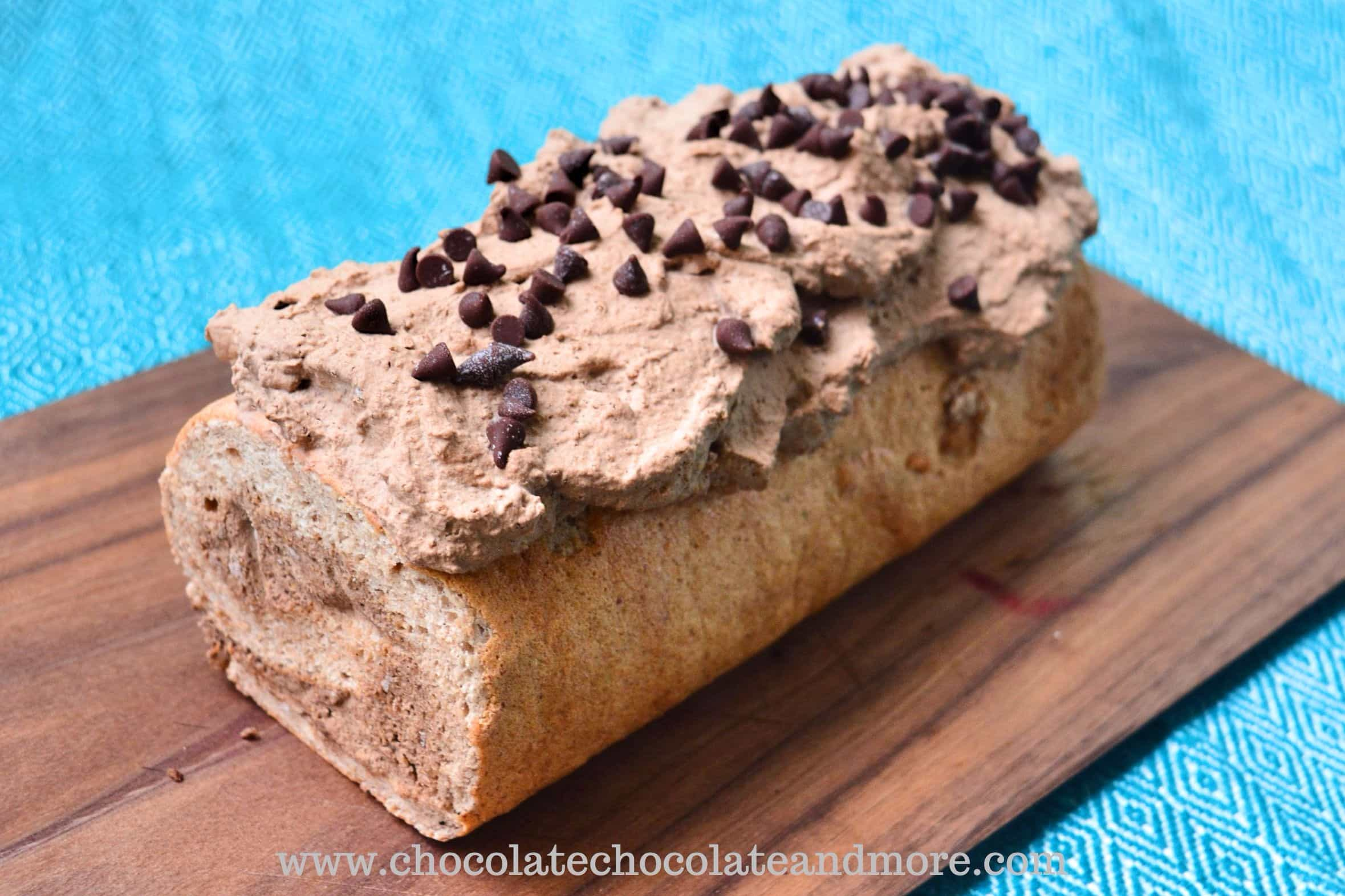a rolled cake topped with chocolate frosting and chocolate chips on a cutting board