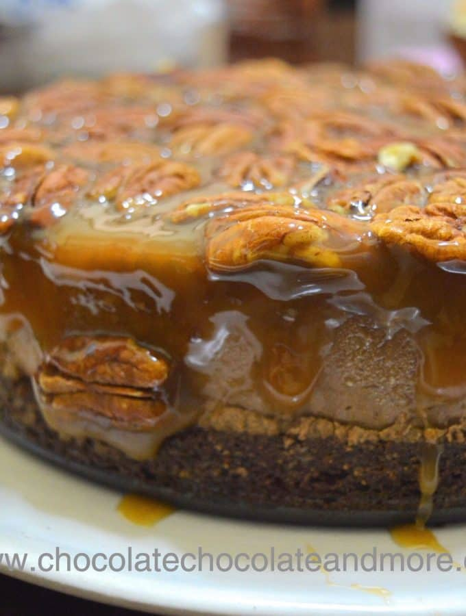 a chocolate mousse cake topped with pecans and dripping with praline sauce