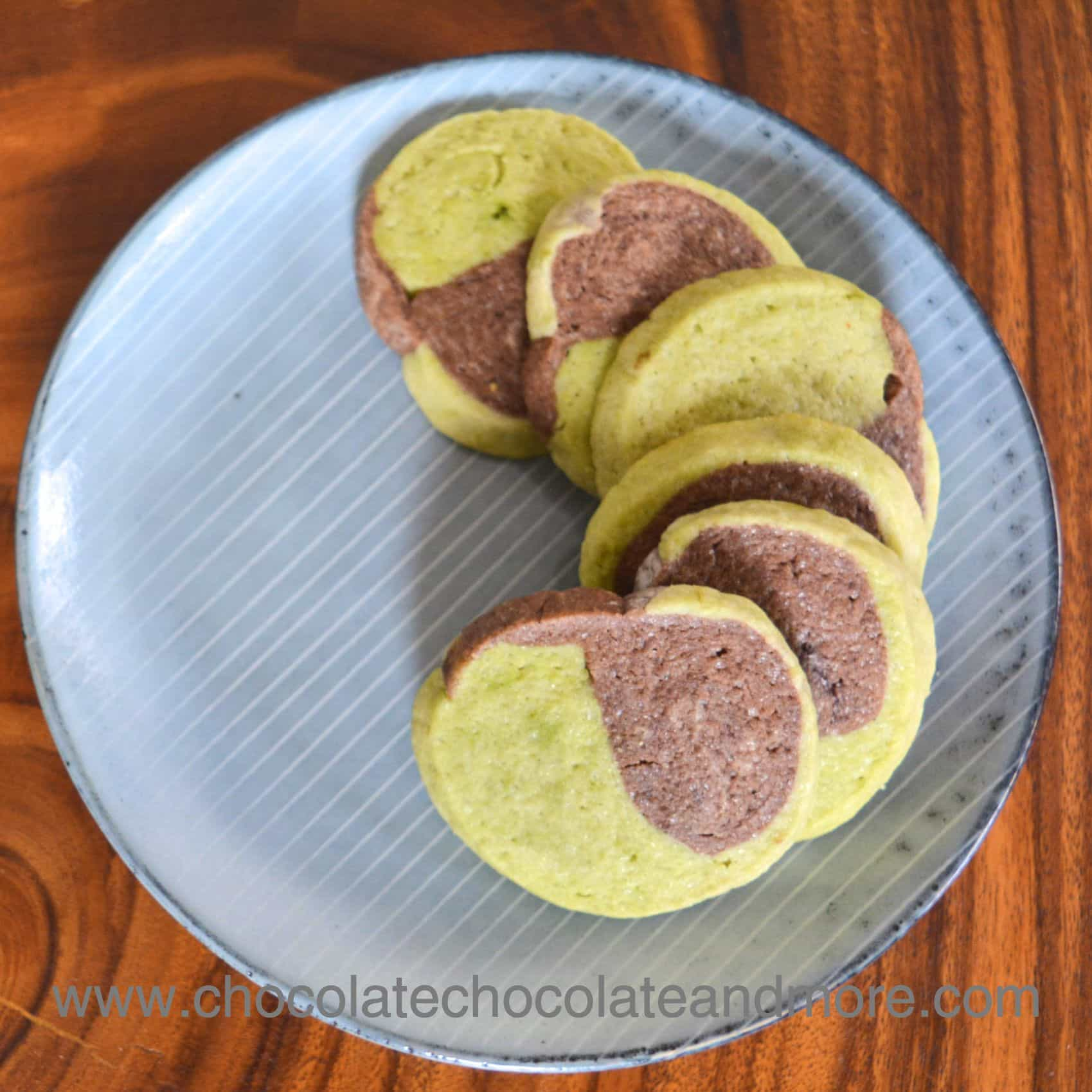 several cookies on a plate with swirled together chocolate and green