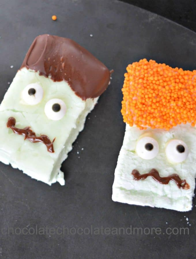 marshmallows decorated with chocolate and sprinkles to look like spooky faces