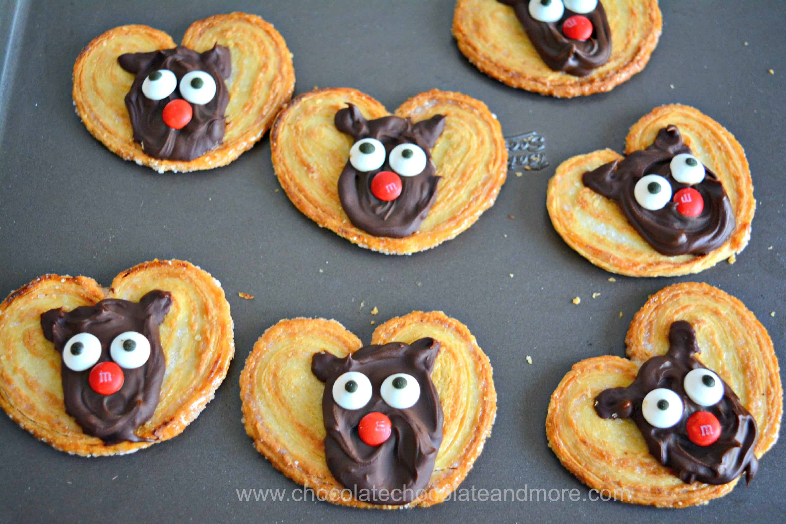 a tray full of palmiers topped with chocolate reindeer faces