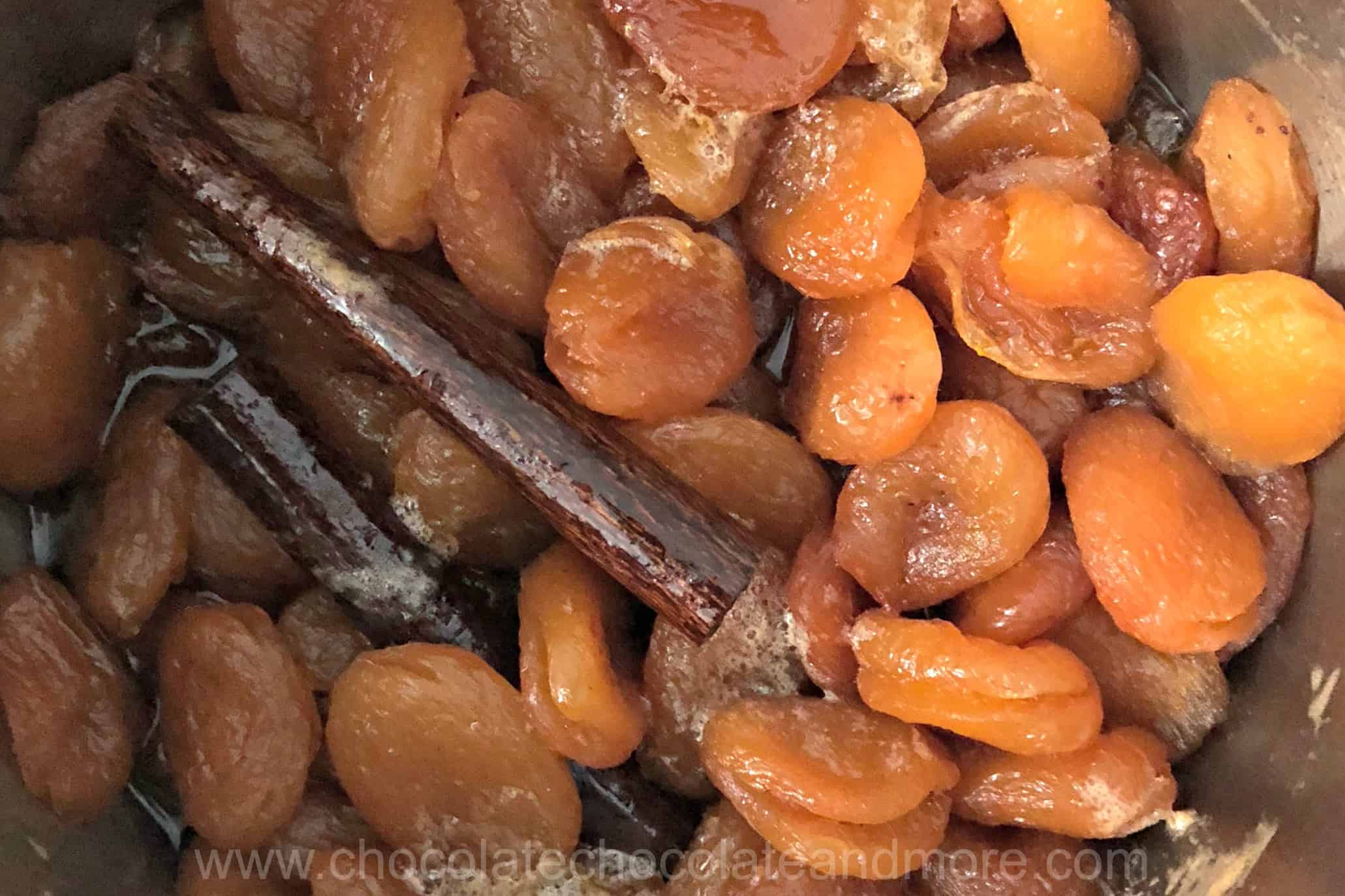 a pot is full of dried apricots soaking with cinnamon sticks