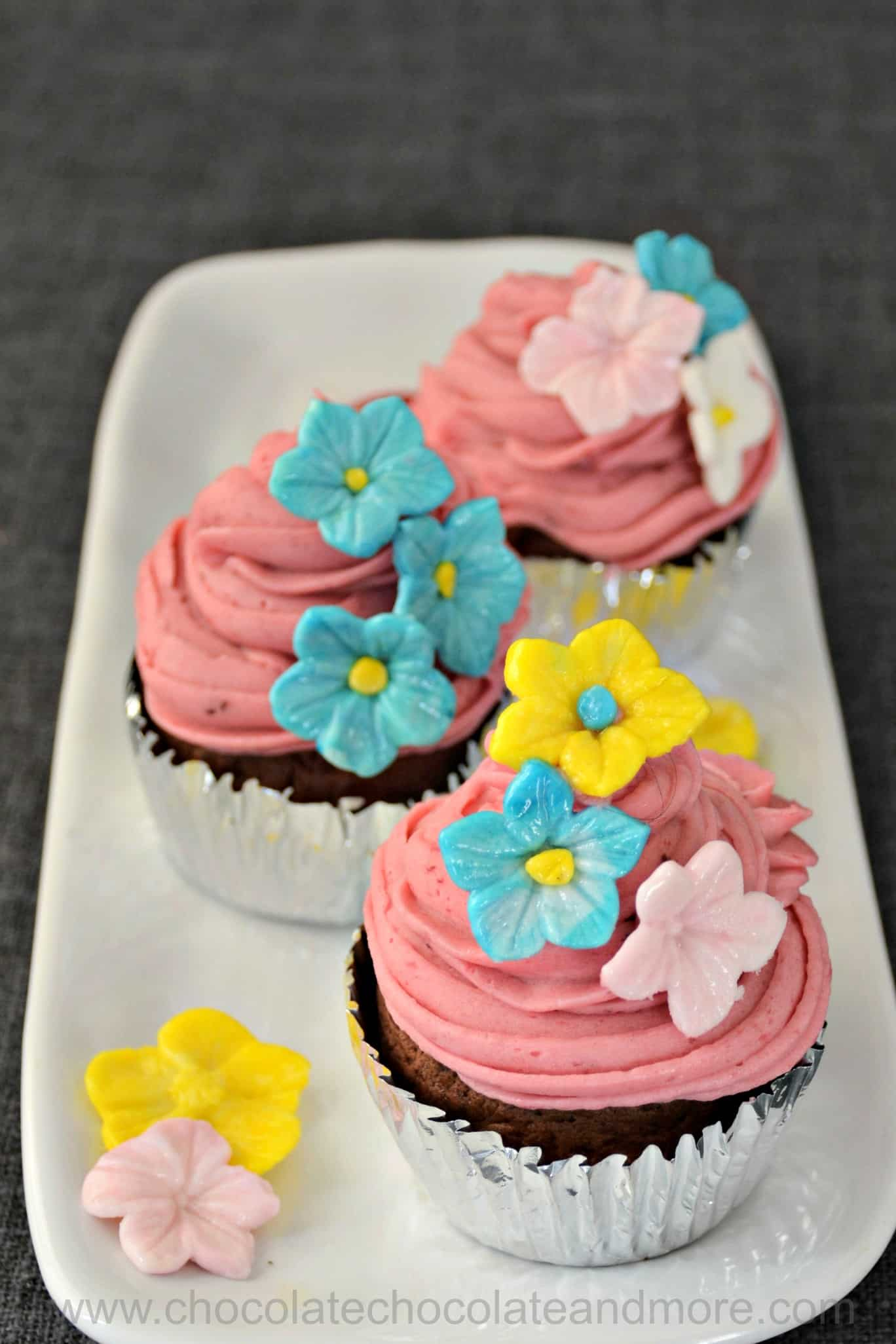 a plate with several cupcakes with purple frosting and delicate flowers made of frosting