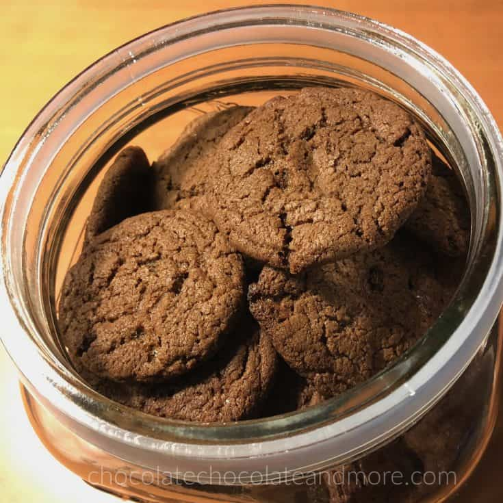 a glass jar full of dark colored cookies