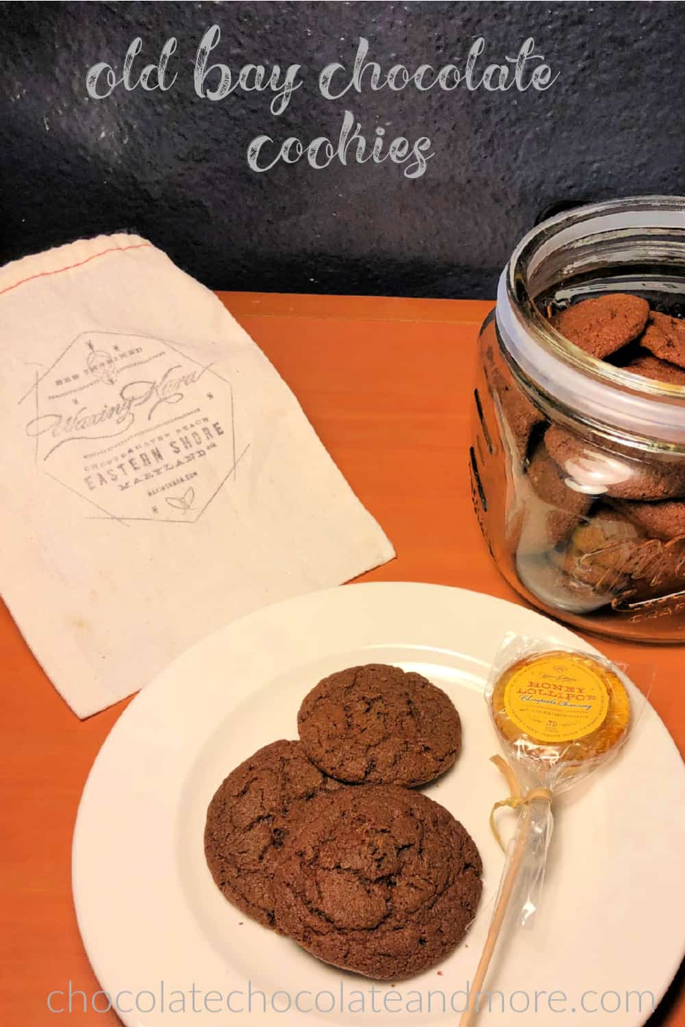 A white plate with three chocolate cookies and a lollipopis in the foreground. A glass cookie jar filled with chocolate cookies is on the right and a muslin sack with the Waxing Kara logo is on the left