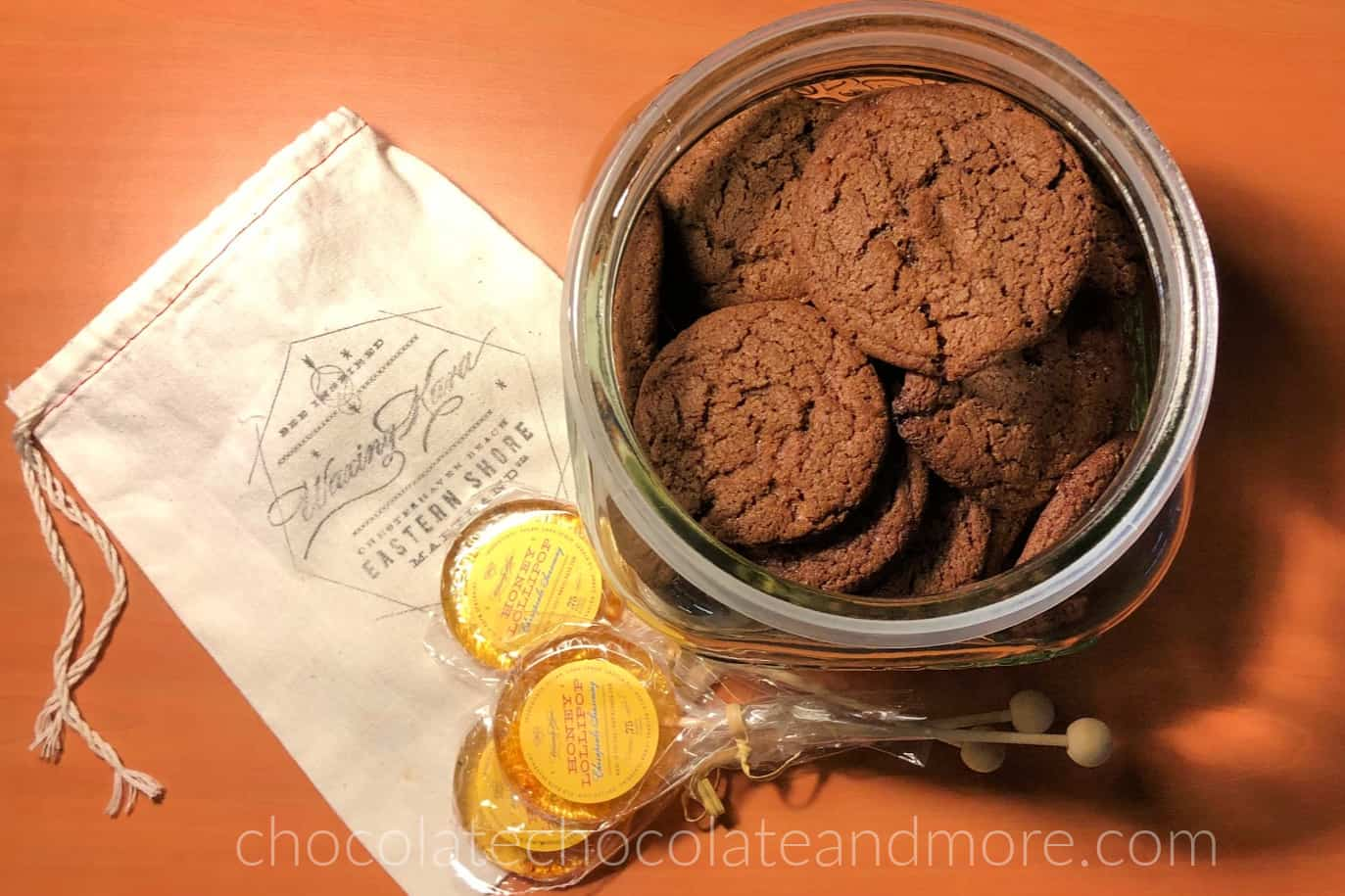 The top view of a glass cookie jar filled with chocolate cookies. Three lollipops are stacked in the front and a muslin sack is to the left. The muslin sack has the Waxing Kara logo on the front.