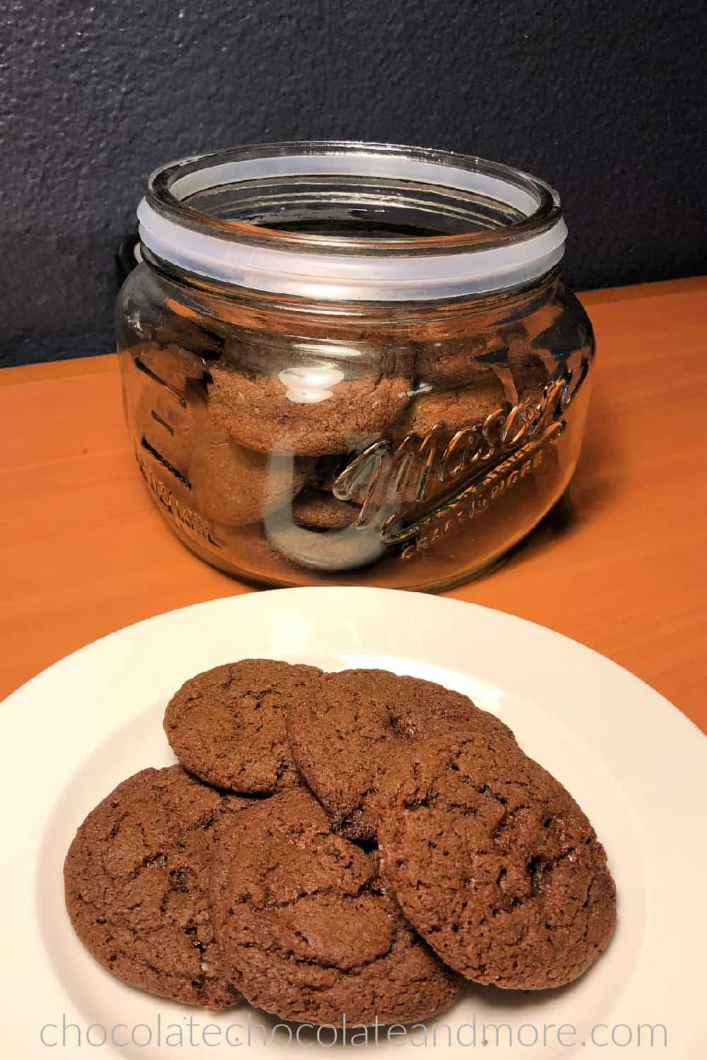 A white plate with five chocolate cookies is in the foreground. The glass cookie jar filled with chocolate cookies is in the background.