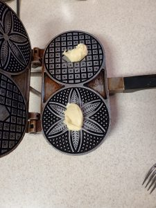 Two balls of cookie dough sitting on a hot pizzelle cookie iron.