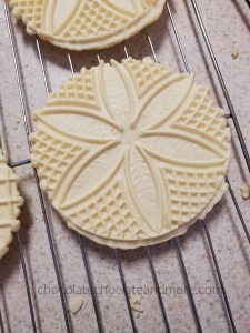 round Italian Anise Pizzelles waffle cookies cooling on a wire rack.  there is a delicate flower pattern baked into the cookies.