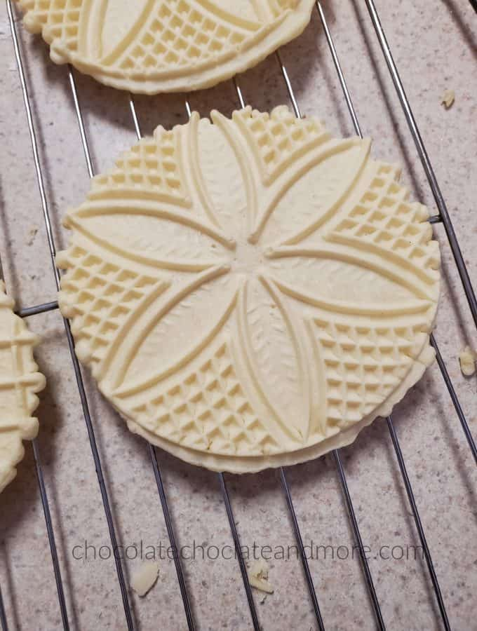 Round flat cookies with decorative imprints cooling on a wire rack.
