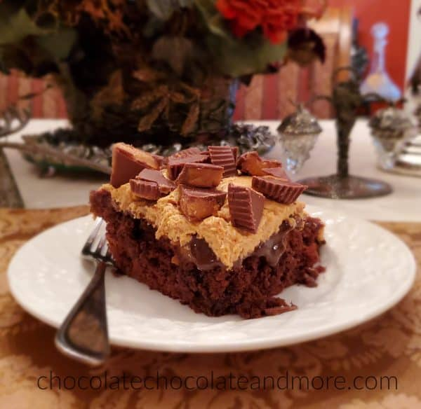 A slice of chocolate cake on a plate covered with peanut butter frosting and peanut butter cups.