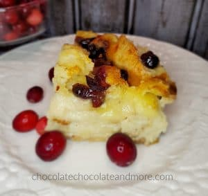 A slice of cranberry brie bread pudding on a white plate with fresh cranberries.