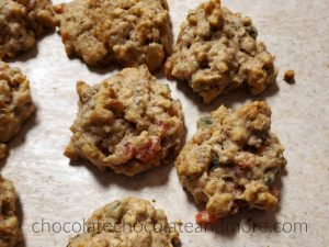 Several fruitcake cookies sitting on a counter with chunks of red and green fruit showing through the dough.