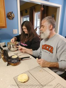 Father and daughter sitting at a kitchen counter make pizzelles on a pizzelle iron.