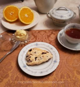 A place setting of china with a cranberry scone with orange butter on the side. There is also a cup of tea and a sliced orange.