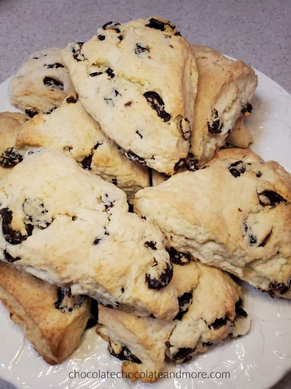A white plate stacked with cranberry scones