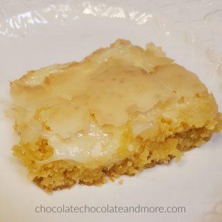 A gooey cream cheese bar on a white plate.
