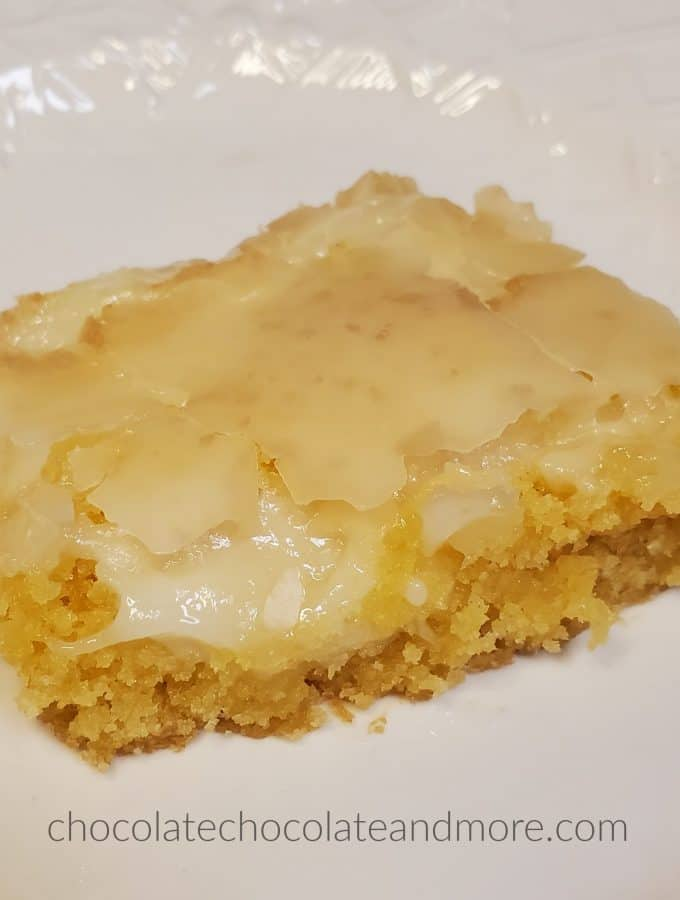 A gooey cream cheese bar on a white plate.