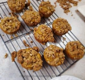 several sweet potato praline muffins cooling on a baking rack. crumbles of praline topping are under the racks