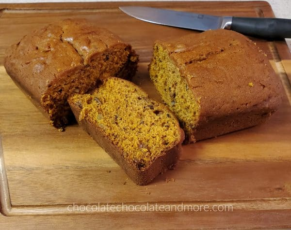 a sliced loaf of pumpkin bread on a wooden cutting board with a knife