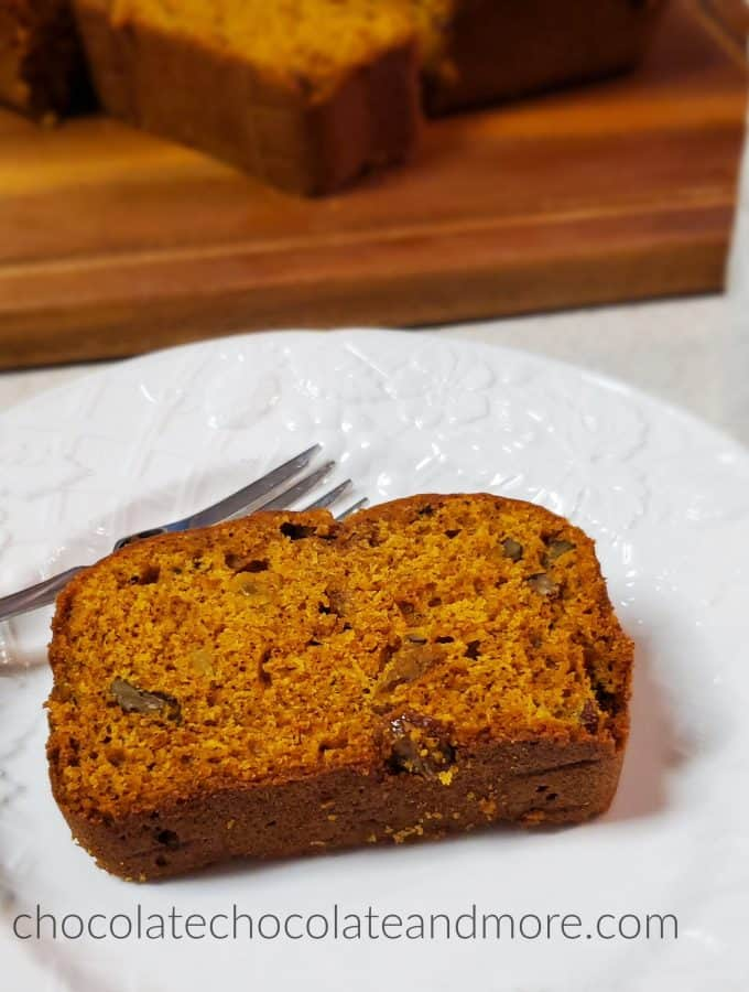 a slice of pumpkin bread on a white plate with a sliced loaf in the background on a wooden cutting board