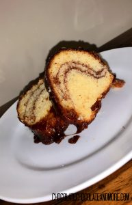 2 slices of Monkey Bread Cake sitting on a circular white plate on a wooden table in front of an off-white background.