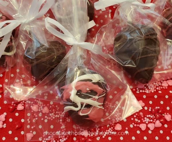 chocolate covered strawberries decorated with pink and white chocolate wrapped in cellophane bags tied with ribbons on a red background covered with candy hearts