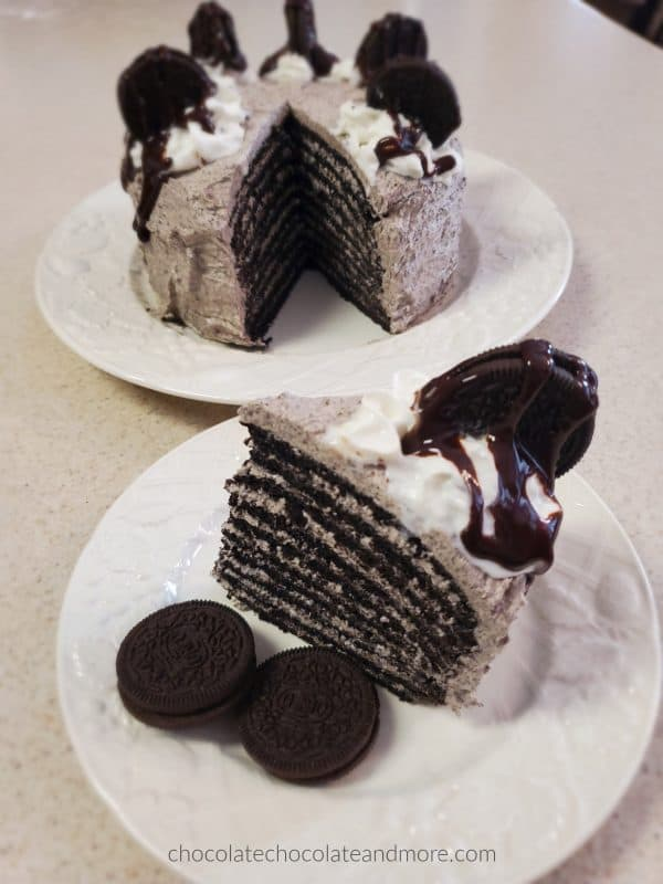 a large slice of a 10 layer two ingredient oreo cake with the whole cake in the background