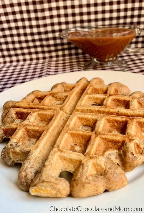 Cinnamon Applesauce Waffles sitting on a white circular plate and a clear gravy boat with cinnamon applesauce glaze sitting behind and a white and black checkered background.