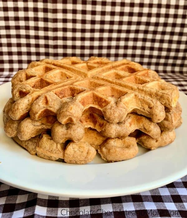 Cinnamon Applesauce Waffles sitting on a white circular plate and a white and black checkered background.