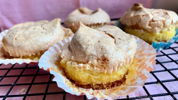 Vanilla Wafer meringue Pie Cups sitting on a metal cooling rack with a pink background.