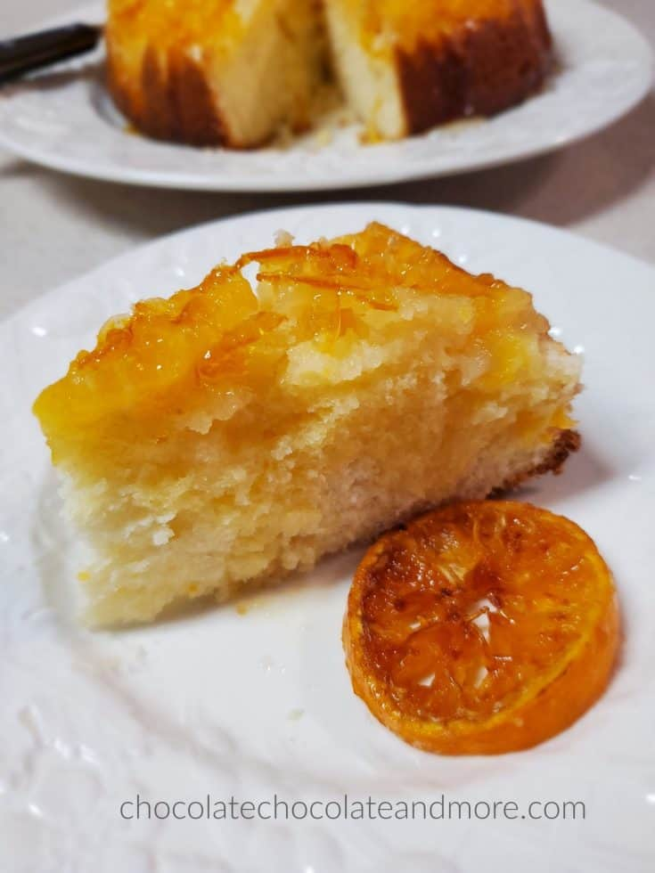 a slice of mandarin upside down cake on a plate with a slice of candied orange