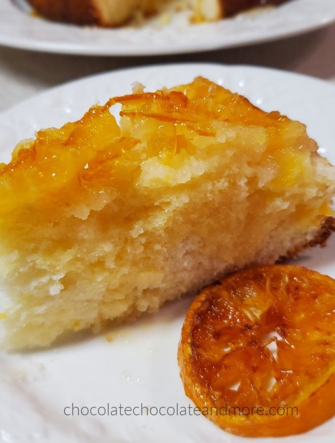 a slice of yellow cake topped with sliced oranges next to a candied orange slice
