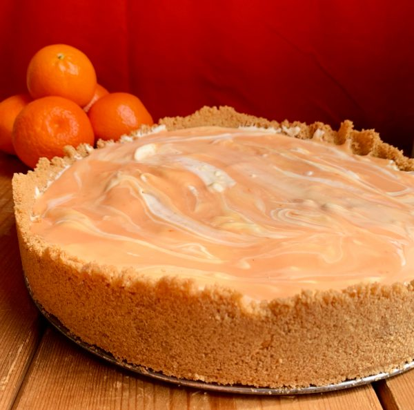 A whole Orange Creamsicle Swirl Cheesecake sitting in front of a red background.