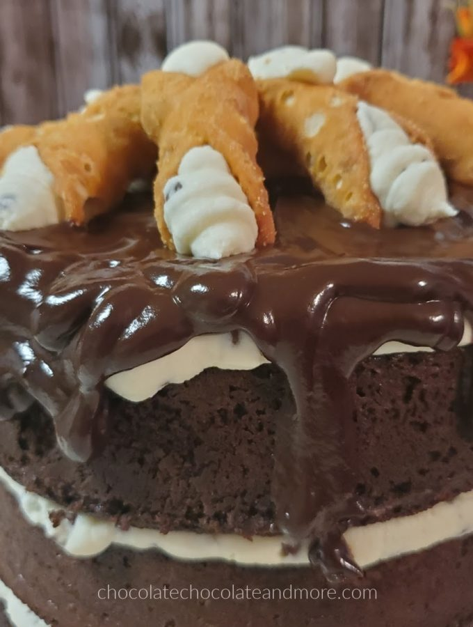 a chocolate layer cake dripping with chocolate frosting and topped with cannolis