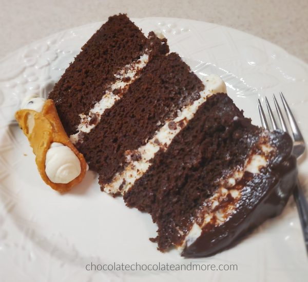 a single slice of triple layer chocolate cake on a white plate with a cannoli