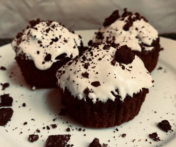 3 Frosted Oreo Brownie Cups sitting on a white plate in front of a white background.