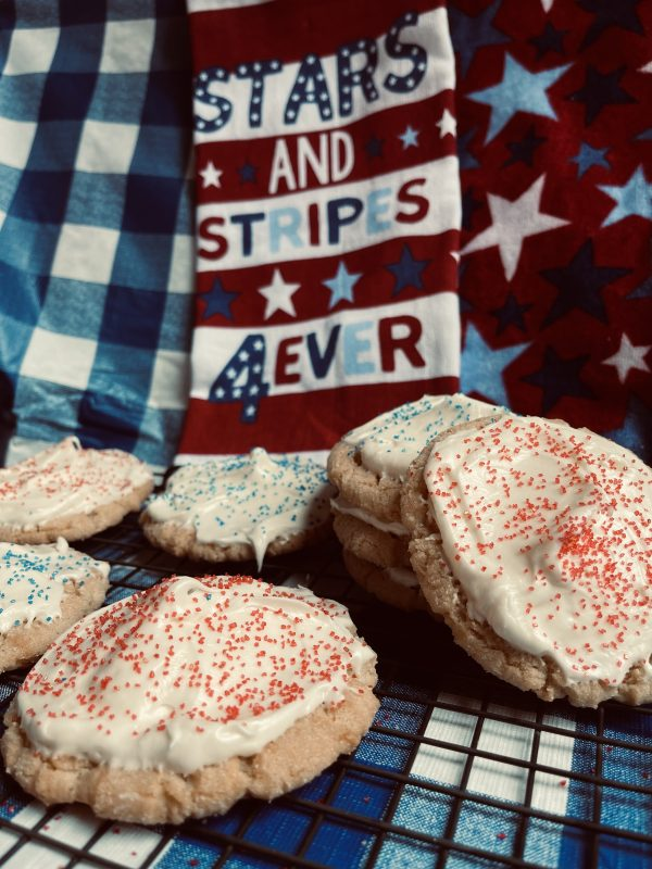 """8 Cream Cheese Frosted Sugar Cookies sitting on a cooling rack on a checkered blue and white background with a """"stars and stripes for ever"""" towel in the back."""
