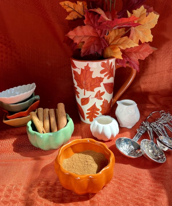 All the ingredients stirred together in an orange pumpkin bowl, bowls shaped like leaves stacked in the back, with a pumpkin shaped bowl filled with cinnamon sticks, a white ceramic pumpkin and owl, a set of teaspoons and tablespoons, and a fall decorated mug holding fall colored leaves.
