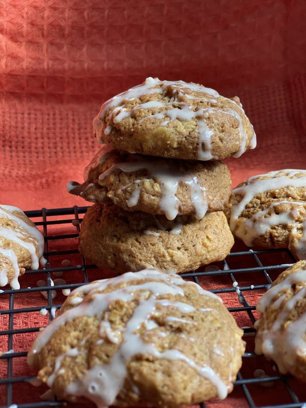 3 Pumpkin Spice Oatmeal Cookies stacked on a cooling rack.